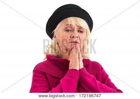 Senior lady praying isolated. Sad woman looking down.
