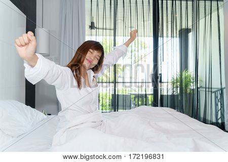 Woman stretching and sitting down on the bed while waking up in the morning with shining light through window
