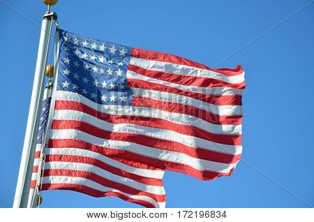 Two american Flag in the breeze on poles