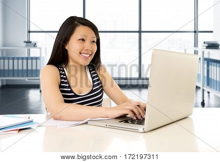 pretty chinese asian ethnic woman working and studying on her laptop at modern office computer desk in female career and business concept