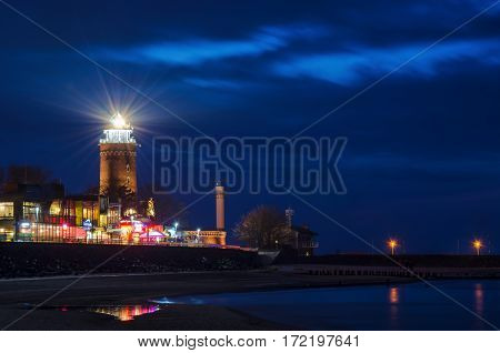 KOLOBRZEG, WEST POMERANIAN / POLAND: Lighthouse and promenade in the cloudy night