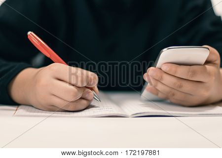 Close Up Of Young Student With Smartphone  Writing To Notebook.