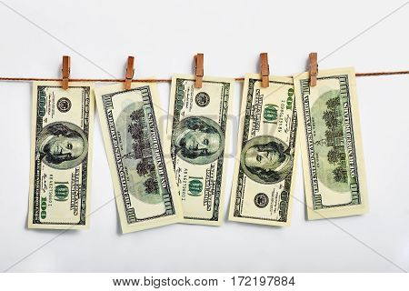 US dollars hanging on clothesline. How to make money.