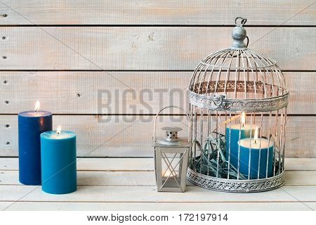 Lantern And Blue Candles Over White Wooden Background. Copy Space.