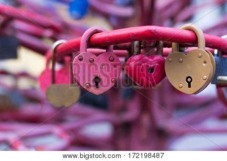 Beautiful metal locks in the form of heart on the bridge