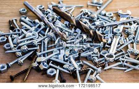 tapping screws made of steel, metal bolts, iron nuts, chrome screws, wood screw, stainless steel bolts and nuts on a wood background