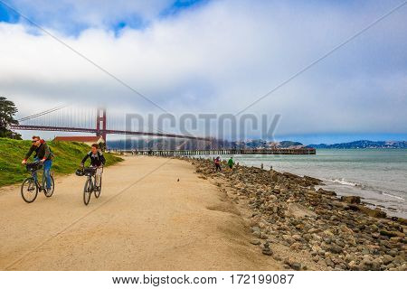 San Francisco, California, United States - August 17, 2016: bike tourists at Crissy Field overlooking on Golden Gate Bridge, icon of San Francisco. Leisure and recreational activities concept.