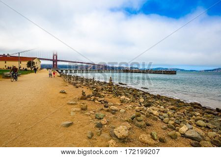 San Francisco, California, United States - August 17, 2016: Golden Gate Bridge with fog from Crissy Field popular beach park for locals and tourists. Leisure and recreational activities concept.