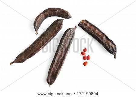 Pods and seeds of the carob tree on a white background. From seed was the name of measure carat