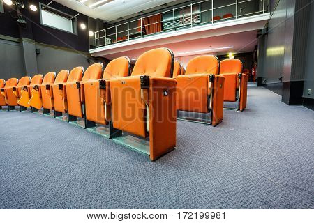 in an small theater there are orange seats in a row