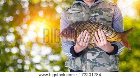 Fisherman With Carp In Hand On A Blurred Background