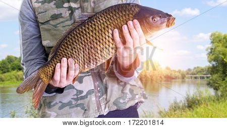 Fisherman With Carp In Hands On A Background Of The River.