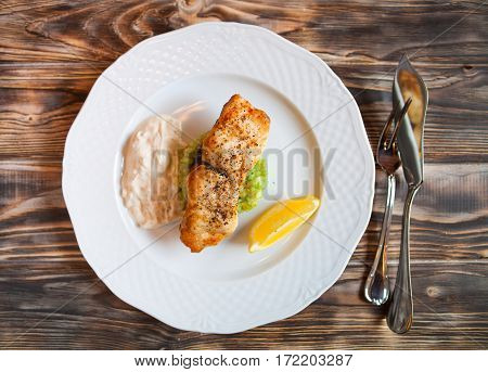 Grilled Fish With Slice Of Lemon And White Sause On Wooden Background.