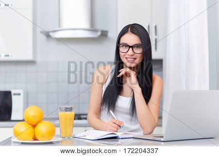Portrait of smiling brunette girl in glasses with long hair studding on kitchen, holding pen in hand and looking at camera. Near on table laptop, books, glass of juice and plate with oranges.