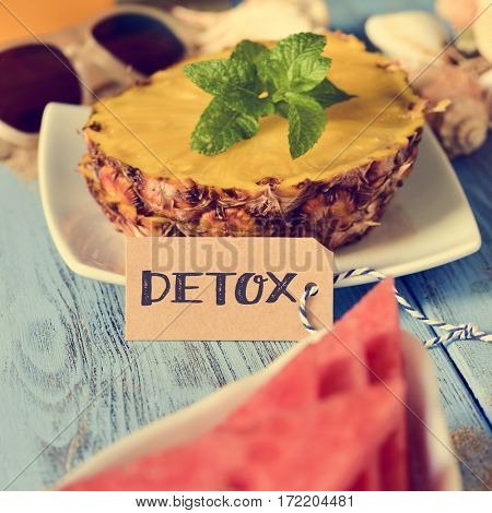 a brown paper label with the word detox in front of a some slices of pineapple and a piece of watermelon on a blue rustic wooden table
