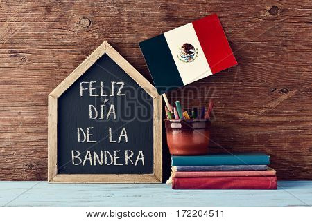 a house-shaped chalkboard with the text Feliz Dia de la Bandera, Happy Flag Day written in Spanish, the flag of Mexico in a pot with some pencil crayons and a pile of old books on a wooden surface
