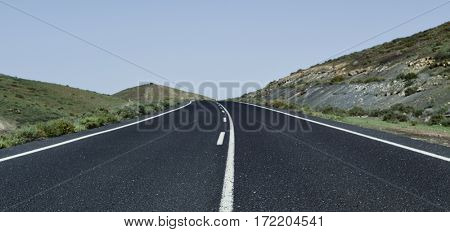 view of a lonely road in a rural landscape with no traffic