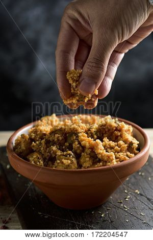 closeup of a young man eating couscous with his fingers from an earthenware casserole placed on a rustic wooden table