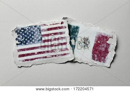 the flag of United States and the flag of Mexico in two aged pieces of paper on an off-white background