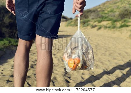 closeup of a young caucasian man seen from behind carrying a transparent plastic bag with leftovers as he walks by a sandy track
