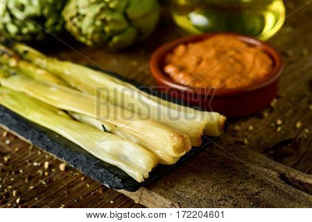 some roasted calcots, sweet onions typical of Catalonia, Spain, and an earthenware bowl with romesco sauce to dip them in it, and a cruet with olive oil on a rustic wooden table