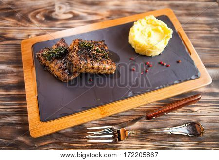 Roasted Ribs With Rosemary And Potatoes On Wooden Cutting Board On Dark Background