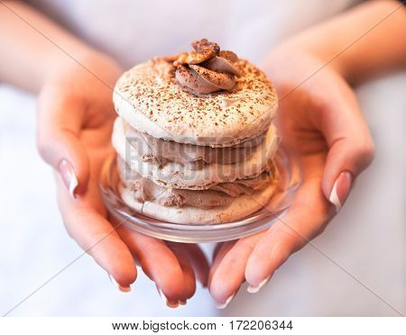 Meringue Cake With A Walnut And Coffee Cream In Female Hands