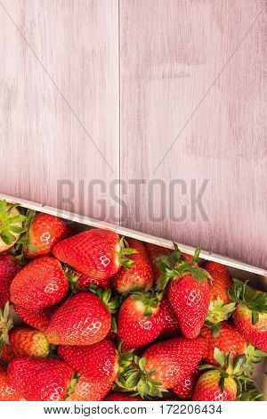 Fresh strawberries in wooden basket on wooden table. Top view with copy space