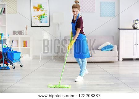 Pretty adult woman moping floor in living room