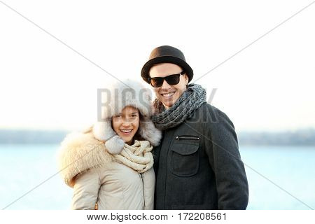 Young couple embracing on blurred river background