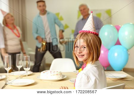 Birthday party. Cute little girl sitting at table