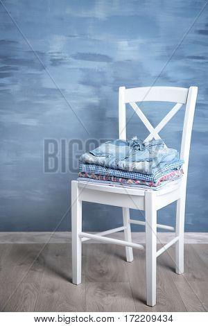 Pile of clothes on wooden chair