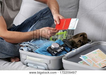 Man packing his grey suitcase in living room