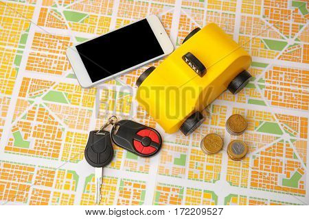 Yellow toy taxi with coins and phone on map