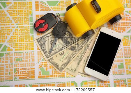 Yellow toy taxi, car key and phone with money on map