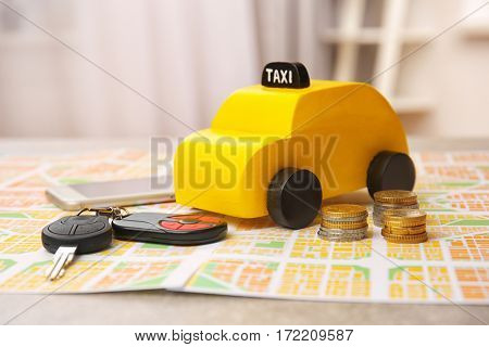 Yellow toy taxi, car key with coins and phone on map