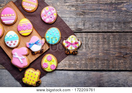 Decorative gingerbread Easter cookies on board and napkin on wooden background
