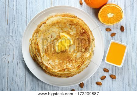 Stack of delicious pancakes with orange on wooden table