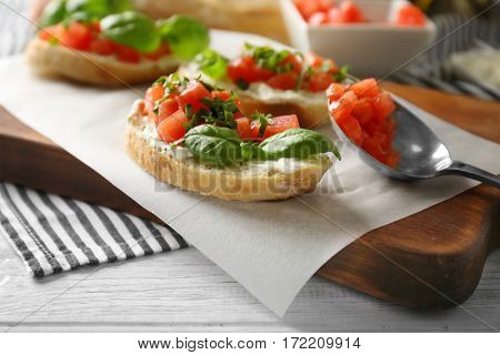Delicious bruschetta with chopped tomatoes and basil on parchment, closeup