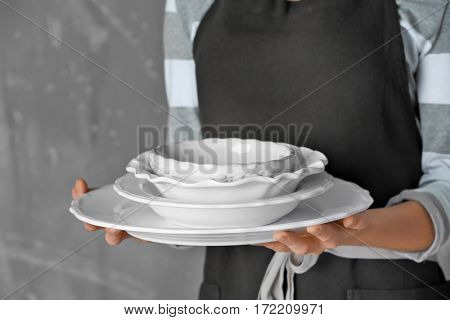 Female hands holding dishes, closeup