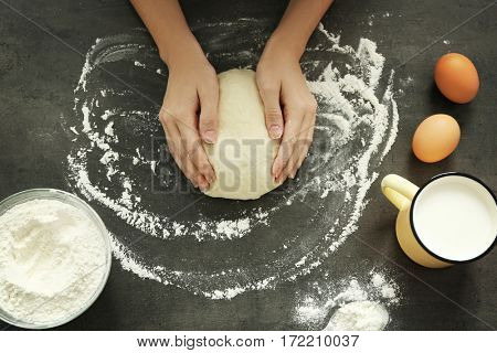 Female hands kneading dough on table, top view
