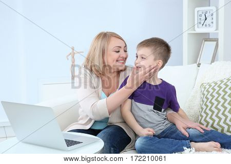 Grandmother and her grandson using laptop at home