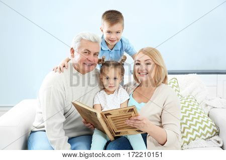 Grandparents looking at photo album with their grandchildren