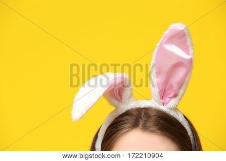 Young woman with bunny ears on color background, closeup