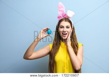 Beautiful young woman with bunny ears and Easter egg on light background