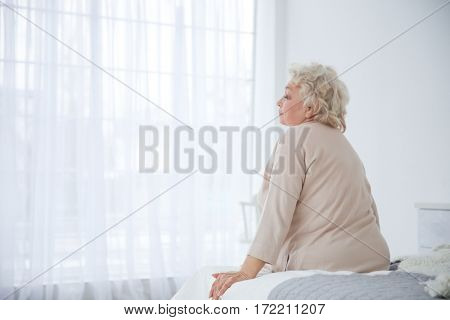 Woman sitting on bed in light room