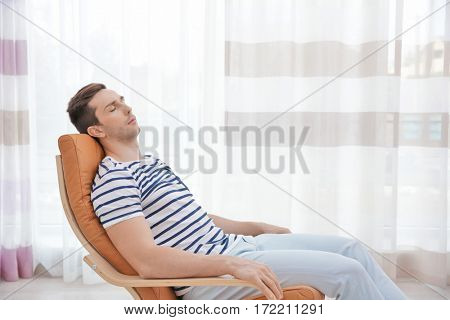 Young man resting on modern deck chair in light room