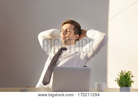 Happy young man having short rest at workplace in light room