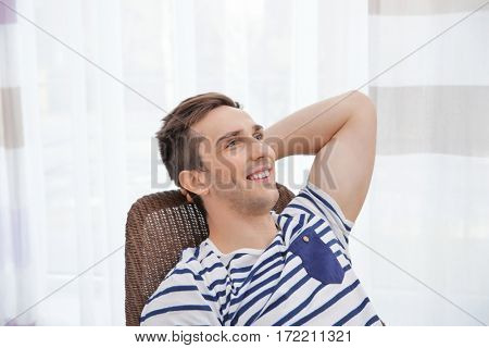 Young man resting on modern chair with hand behind his head in light room