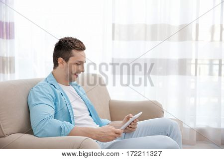 Young man resting on couch with tablet computer in light room